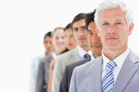 single line: Close-up of a single line of business people with focus on the first person against white background