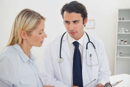 examination room: Doctor in his examination room talking to his female patient