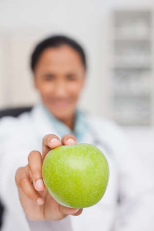 green apples: Big green apple being held by a doctor sitting at her desk