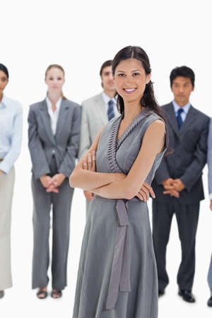 team from behind: Close-up of a woman with a business team behind her against white background