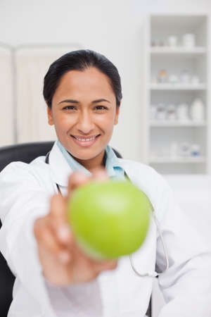 practitioner: Smiling practitioner holding a delicious green apple