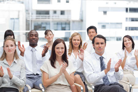 applaud: A group of colleagues look ahead and applaud as they sit next to each other LANG_EVOIMAGES