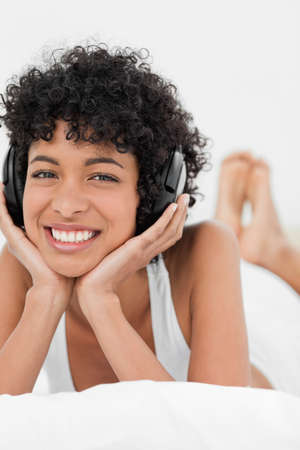 frizzy: Close-up of a frizzy haired woman smiling while listening to music with headphone LANG_EVOIMAGES