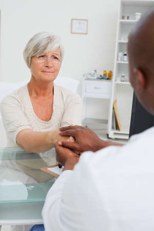 reassurance: Doctor holding sad mature patients hand