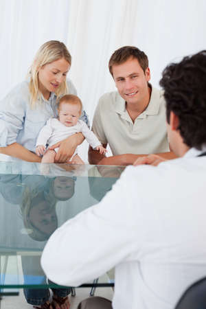 family physician: Male doctor talking to young family