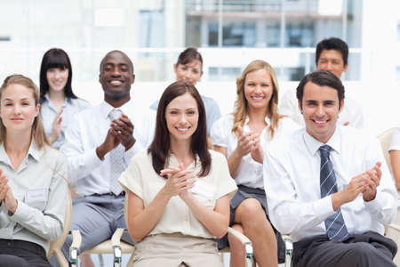 applaud: A group of smiling colleagues look ahead and applaud as they sit next to each other LANG_EVOIMAGES