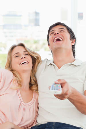 programme: A close up shot of a man and woman laughing together at a television programme.
