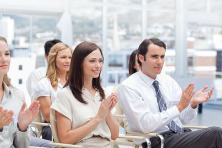applaud: Colleagues looking ahead and applaud as they sit next to each other