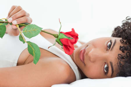 frizzy: Portrait of a beautiful frizzy haired woman lying on her bed with a rose in a bright room
