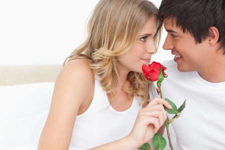 mujer alegre: La mujer y el hombre miran a los ojos, ya que sonríen y que sostiene una rosa