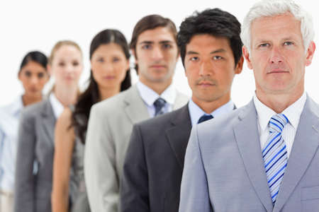 single line: Close-up of business people in a single line with focus on the first person against white background