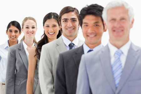 single line: Close-up of smiling business people in a single line with focus on the fifth person against white background