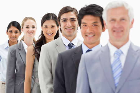 single line: Close-up of smiling business people in a single line with focus on the fourth person against white background