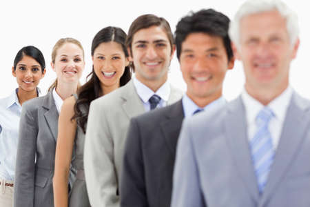 single line: Close-up of smiling business people in a single line with focus on the last person against white background