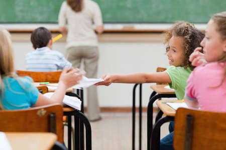 handing over: Little girl handing over sheets LANG_EVOIMAGES