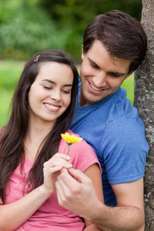 countryside loving: Young smiling couple standing against a tree while holding a yellow flower together
