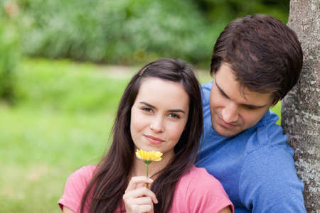 countryside loving: Young woman smelling a beautiful flower with her boyfriend behind her