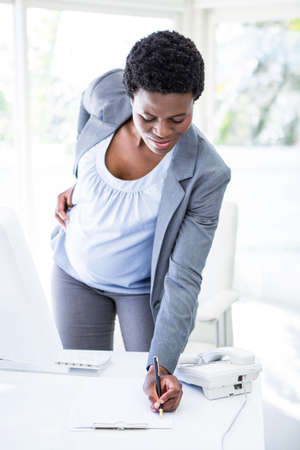 filling out: Smiling pregnant businesswoman at work filling out documents