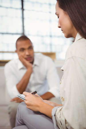 interacting: Counselor writing while patient interacting at clinic