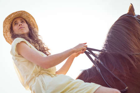 reigns: Young happy woman riding her horse in the countryside