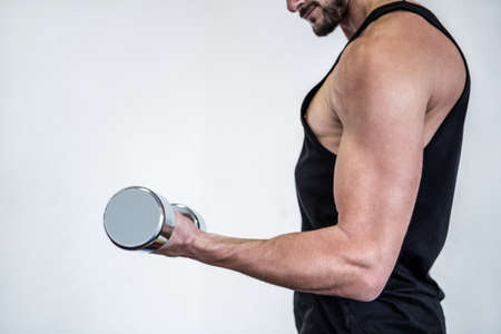 man working out: Fit man working out with dumbbell at crossfit gym