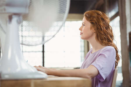 electric fan: Side view of woman working by electric fan at office