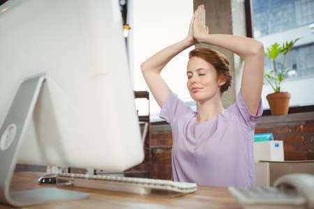 manos levantadas: Businesswoman meditating with hands raised at desk