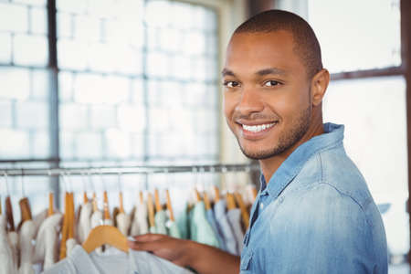 clothes rack: Portrait of smiling man holding shirt by clothes rack at shopping mall