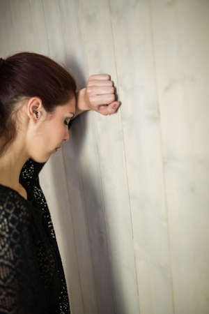 tied hair: Depressed woman with eyes closed while leaning against wall LANG_EVOIMAGES