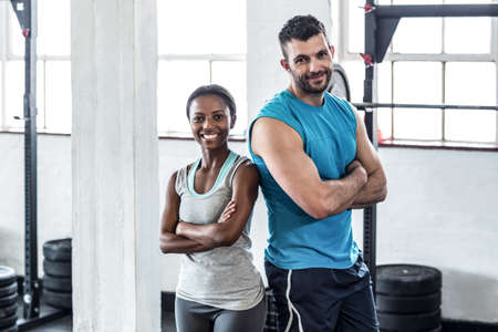 giving back: Muscular couple giving back to back in crossfit