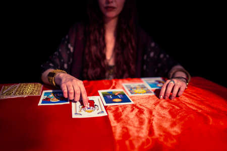 teller: Fortune teller pointing at tarot card while sitting at table LANG_EVOIMAGES