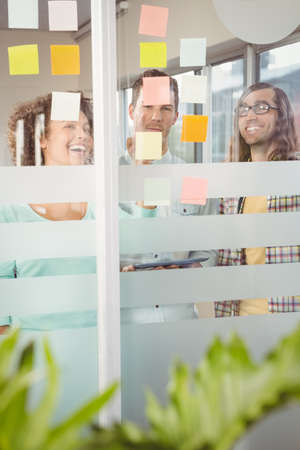 hapy: Hapy business people looking at adhesive notes in creative office LANG_EVOIMAGES