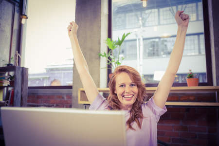 hands raised: Portrait of happy woman with hands raised at creative office LANG_EVOIMAGES