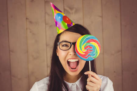party hat: Pretty hipster with party hat and lollipop on wooden background LANG_EVOIMAGES