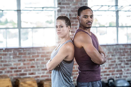 giving back: Serious fit couple giving back to back in crossfit gym LANG_EVOIMAGES