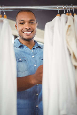 clothes rack: Smiling man searching for shirt in clothes rack at shopping mall