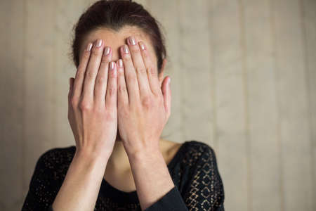 hands covering face: Woman covering face with hands while standing against wall LANG_EVOIMAGES