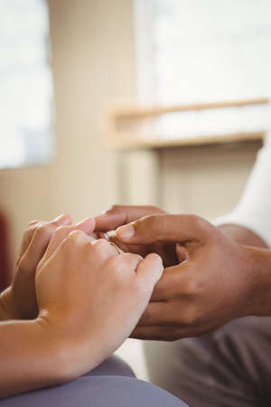 counselling: Cropped image of female counselor holding man hand while counselling man in clinic