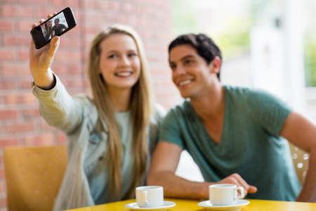 tomando refresco: Los estudiantes que toman autofoto en el café en la universidad LANG_EVOIMAGES