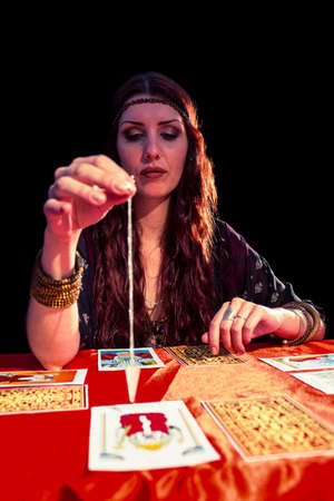 pendulum: Female fortune teller looking at pendulum while sitting at table LANG_EVOIMAGES