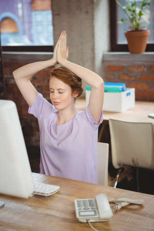 manos levantadas: Empresaria meditando con las manos levantadas en la oficina creativa LANG_EVOIMAGES