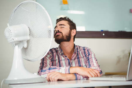 electric fan: Business man sitting on chair in front of electric fan at creative office
