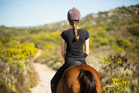 reigns: Young woman riding her horse the countryside LANG_EVOIMAGES