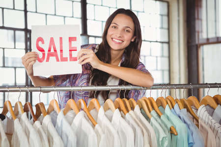 clothes rack: Portrait of smiling woman holding sale sign and leaning on clothes rack in store