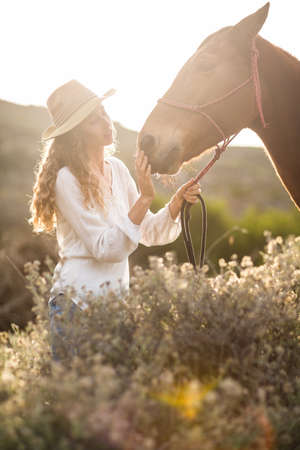 reigns: Young happy woman with her horse in the countryside LANG_EVOIMAGES