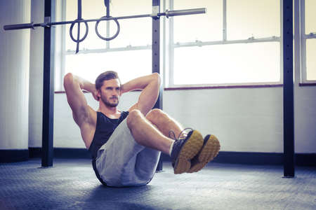 sit up: Fit man working out in studio at crossfit gym LANG_EVOIMAGES