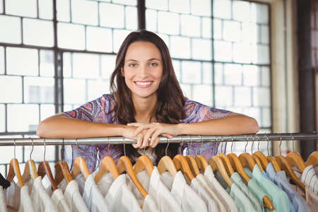 clothes rack: Portrait of smiling woman leaning on a clothes rack in a shop