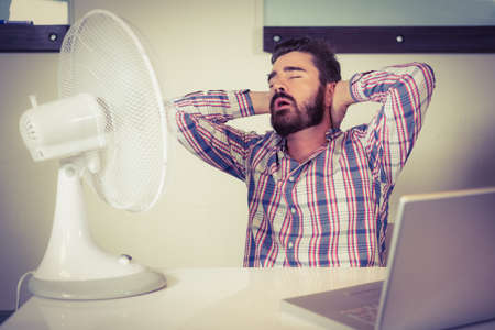 electric fan: Man with mouth open sleeping by electric fan at creative office