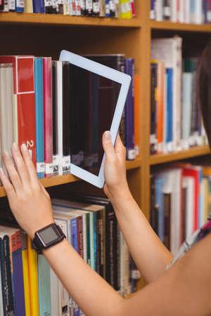 bookshelf digital: Hands keeping digital tablet with blank screen in bookshelf at library LANG_EVOIMAGES