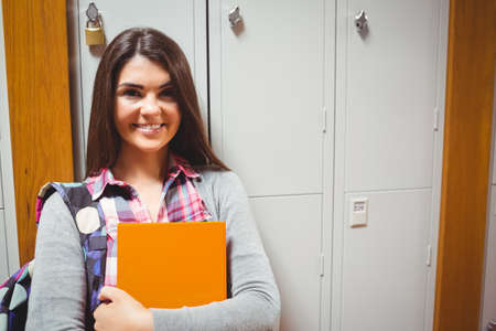 keeping room: Portrait of smiling student against lockers in room LANG_EVOIMAGES